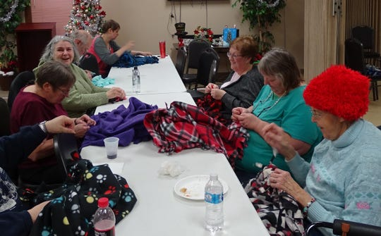 Volunteers knot the fringes on fleece blankets on Tuesday at the Crawford County Council on Aging. From left are Mary Stuckert, Gerry Sams, John Sams, Amy Ward, Bev Whaley, Gloria Pelfry and Marilyn Smith.