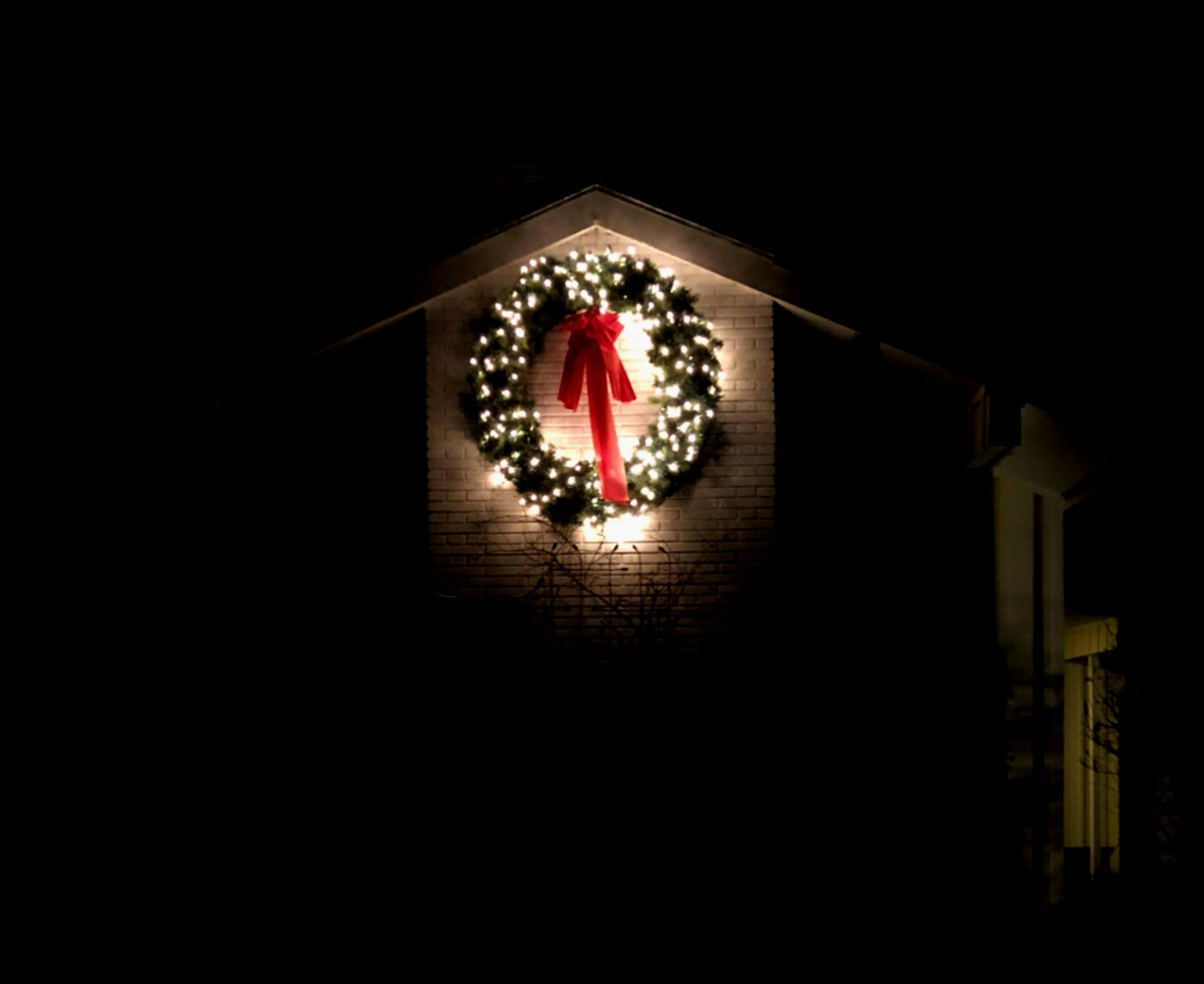 A Christmas wreath lights up the chimney of a home in South Burlington on Tuesday, Dec. 10, 2019.