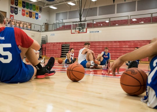 Senior Colby Swain leads the rest of the Zane Trace basketball team in stretches before they start practice on Dec. 9, 2019.