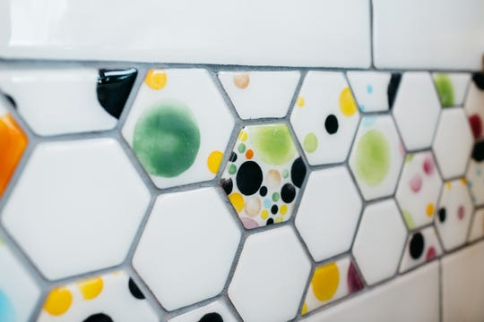 Glass tiles made by Brazee Street Studios are part of the decor at Waggle Breakfast and Bowls