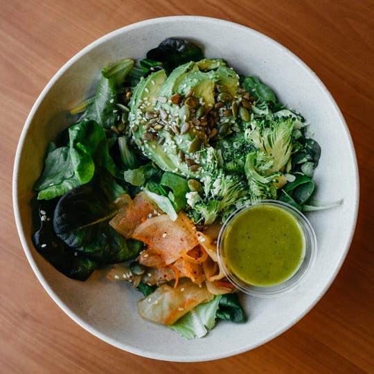 The ginger soy salad bar from Waggle Breakfast and Bowls is made with waggle greens, broccoli, sweet potatoes, kimchi, seed mix, avocado and ginger soy dressing