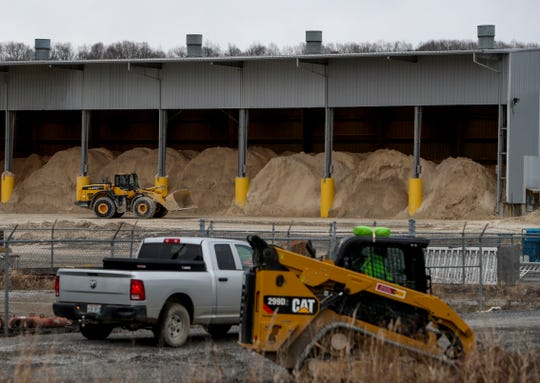 Workers operate machinery and, in the background, shuttle gypsum into bays at TVA Cumberland Fossil Plant in Cumberland City, Tenn., on Tuesday.
