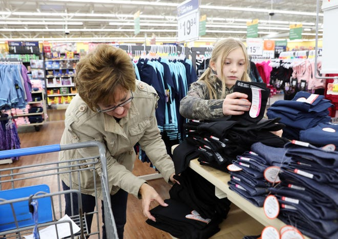 LeeAnne Shriver, 9, and Melody Lowe look at clothing during the Christmas Castle event at Walmart in Coshocton on Tuesday. The Salvation Army raised money to help 432 kids get clothing this year.