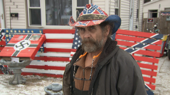 """William Stark of Des Moines displayed """"flags,"""" painted on wooden pallets, Dec. 10, 2019, outside his home in the 6000 block of Southwest 15th Street. One of the painted pallets featured a swastika."""
