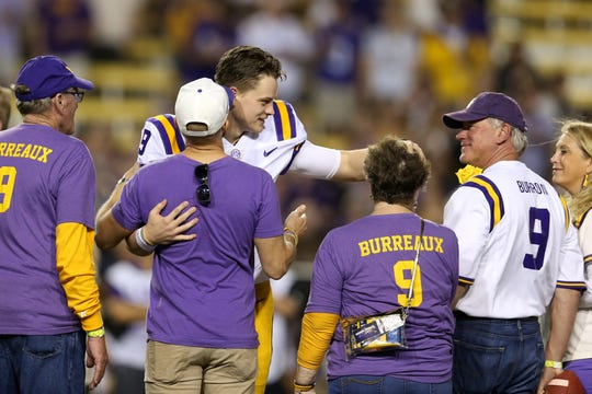 LSU Tigers quarterback Joe Burrow (9) greets family members as he and other seniors are honored before a game against the Texas A&M Aggies at Tiger Stadium on Nov. 30, 2019.