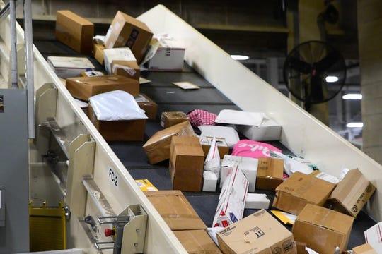 Packages flow through the U.S. Postal Service Des Moines Network Distribution Center on Dec. 11, 2019.