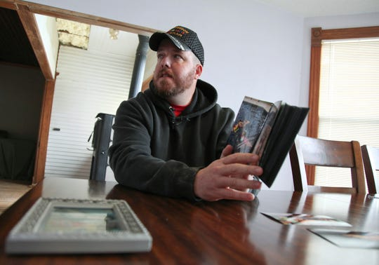 In this Nov. 1, 2019, photo, Gabe Steele holds a photo album in his home in West Point, Iowa, and talks about the accidental fatal shooting of his wife, Autumn Steele, by a Burlington, Iowa police officer in 2015.