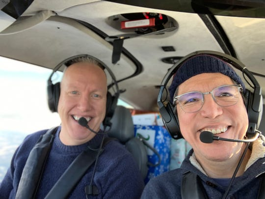 Jerry Fullmer (left) and Santiago Chamorro, vice president of GM Global Connected Services (right), seen flying to Ludington, Mich. to deliver presents for local foster care agencies.