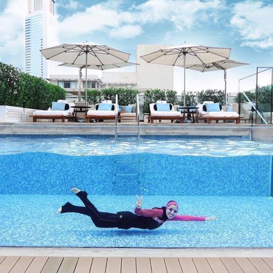 Haute Hijab CEO Melanie Elturk swims in a pool wearing her Speedo modest swimwear