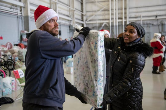 Volunteers Gary Shultz of Farmington Hills And Jasmine Brown of Ann Arbor, help load gifts onto a truck  during the Operation Good Cheer at the Oakland County Airport in Waterford, Friday, Dec. 6, 2019.
