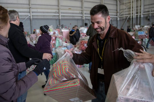 Pilot Eric Kaufman, center, helps load gifts onto a truck during the Operation Good Cheer at the Oakland County Airport in Waterford, Friday, Dec. 6, 2019.