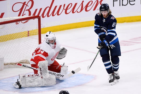 Winnipeg Jets' Kyle Connor (81) deflects a shot in front of Detroit Red Wings goaltender Eric Comrie (34) during the first period of an NHL hockey game, Tuesday, Dec. 10, 2019, in Winnipeg, Manitoba.