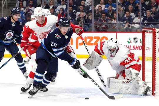 Winnipeg Jets center Jack Roslovic (28) tries to shoot on Detroit Red Wings goaltender Eric Comrie (34) in the second period at Bell MTS Place in Winnipeg, Manitoba on Dec. 10.