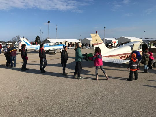 Operation Good Cheer volunteers at Roben-Hood Airport (Big Rapids, Mich.) form a human chain to transfer gifts from aircraft into moving vans for delivery to local foster care agencies.