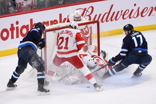 Winnipeg Jets' Adam Lowry (17) scores a short-handed goal on Detroit Red Wings goaltender Eric Comrie (34) as Dennis Cholowski (21) looks for the rebound during the first period of an NHL hockey game, Tuesday, Dec. 10, 2019, in Winnipeg, Manitoba.