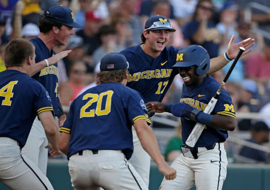 Michigan's Ako Thomas, right, is congratulated by teammates after scoring against Vanderbilt during the first inning in Game 3 of the NCAA College World Series baseball finals in Omaha, Neb., Wednesday, June 26, 2019. (AP Photo/Nati Harnik)