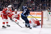 Winnipeg Jets' Patrik Laine (29) scores on Detroit Red Wings goaltender Eric Comrie (34) during the second period.
