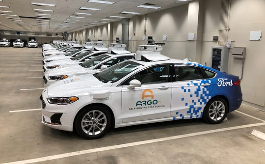 A row of Ford Fusion Hybrid sedans outfitted with sensors and other self-driving equipment are parked in Argo's test garage in Pittsburgh, Pennsylvania, U.S. September 19, 2019.