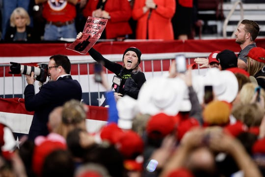 A protester calls out before she is removed as President Donald Trump speaks at a campaign rally, Tuesday, Dec. 10, 2019, in Hershey, Pa.