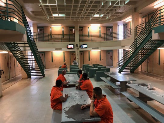 Inmates spend time in a common area outside of their cells at the Genessee County Jail, Dec. 5, 2019.
