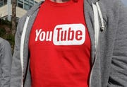 A YouTube logo on a t-shirt worn by a person near a YouTube office building in San Bruno, Calif.
