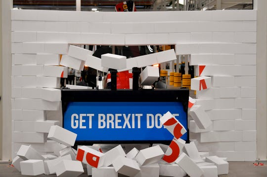 Britain's Prime Minister Boris Johnson drives a JCB machine through a symbolic wall with the Conservative Party slogan 'Get Brexit Done' in the digger bucket, during an election campaign event at the JCB manufacturing facility in Uttoxeter, England, Tuesday Dec. 10, 2019.