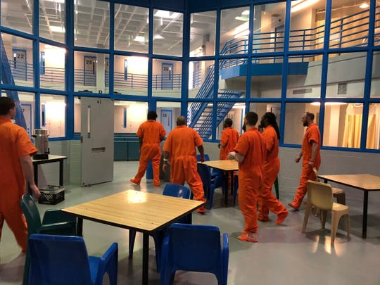 Inmates leave a common area at the Genessee County Jail.