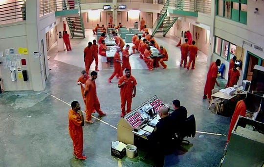 Inmates spend time in a common area at the Genessee County Jail.