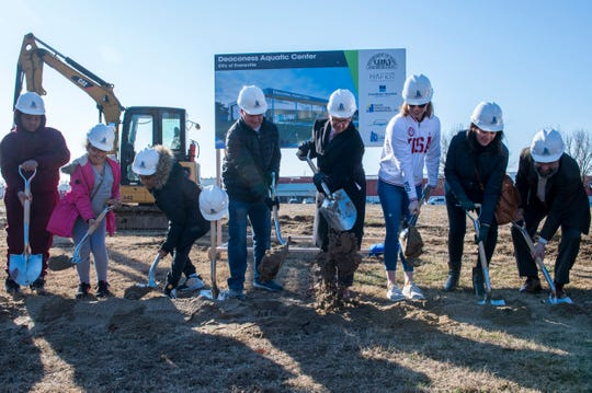 Two-time Olympic gold medalist Lilly King (third from right) turns dirt during the groundbreaking ceremony of the Deaconess Aquatic Center Wednesday, across the street from Bosse Field.