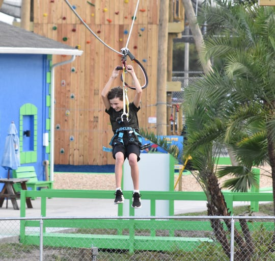 Tre Sovich, 12, of Cape Coral looks at the turtles and fish in the pond as he zips down the main zip line at Gator Mike's in Cape Coral. The 550-foot zip line can reach speeds of 26 miles per hour.