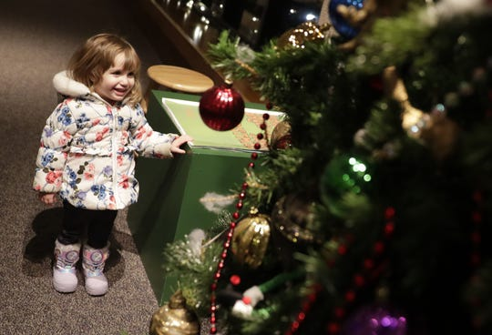 Isabel Cowell, 2, of Green Bay, laughs as she interacts with Bruce the Spruce on Dec. 4 at the Neville Public Museum of Brown County in Green Bay. The museum has been the talking tree's holiday home since 2006, but his beginnings date back to the H.C. Prange Co. department store in the 1970s.
