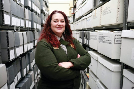 In this Wednesday, Dec. 4, 2019 photo, Yellowstone National Park Archivist Anne Foster stands among rows of historic documents stored in the archives at the Park's Heritage and Research Center in Gardiner, Mont. (Justin Post/Livingston Enterprise via AP)