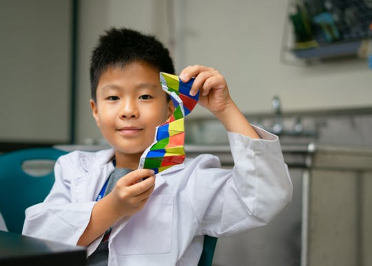 Jase Cho holds an origami DNA helix.