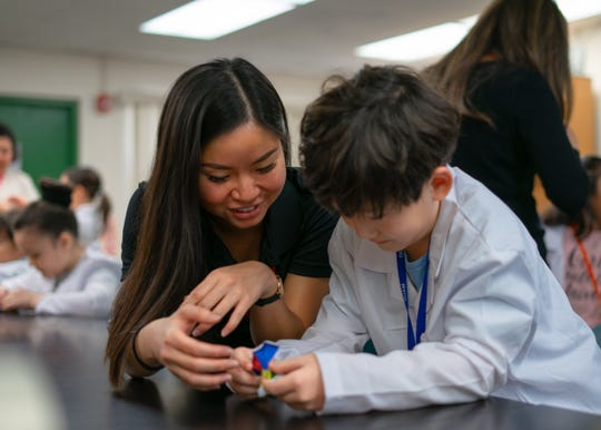 Karla Wang, Guam GENE-ius instructor, assists student Jayden Yi with a science project.