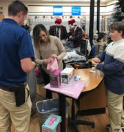 Braxton Revelett, 10, (right) is assisted by Jessica Isonhood and husband, HPD Detective Jake Isonhood during Cops and Kids on Tuesday (Dec. 10, 2019)