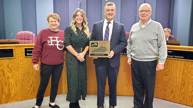 """Kentucky League of Cities' Bryanna L. Carroll (second from left), Henderson Mayor Steve Austin (right) and Henderson Commissioner Patti Bugg (left) present state Senator Robby Mills with a 2019 """"Friend of Kentucky Cities"""" award at the Tuesday Henderson City Commission meeting."""