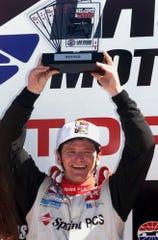 Sam Schmidt of Las Vegas lifts the trophy after winning the IRL Vegas.com 500 at the Las Vegas Motor Speedway in Las Vegas on Sunday Sept. 26 1999.