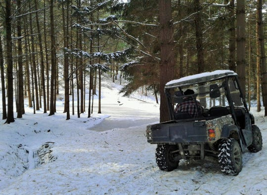 After a fresh snowfall, Myers' all-terrain utility vehicle is the best way to cruise through the conifers to examine his ponds.