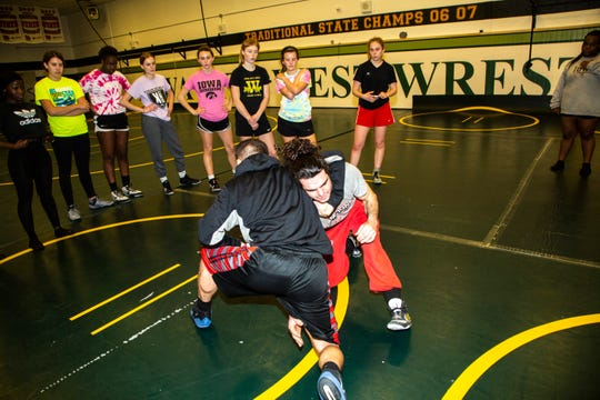 Iowa City West coach Justin Koethe demonstrates a maneuver with coach Elijah Sullivan during a girls' wrestling practice, Monday, Dec. 9, 2019, at West High School in Iowa City, Iowa.