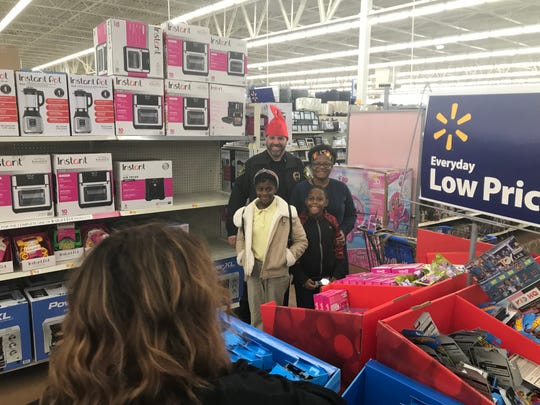 Milan Police Chief Bobby Sellers pauses with his shopping partners, Tidaris Young and Seqouri Glenn, as they shop with a cop at Wal-Mart.