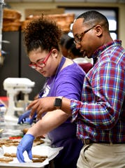 Delisa Gladney places uncooked cookies on parchment paper as Tim Hayes explains the cooking process of gingerbread cookies.