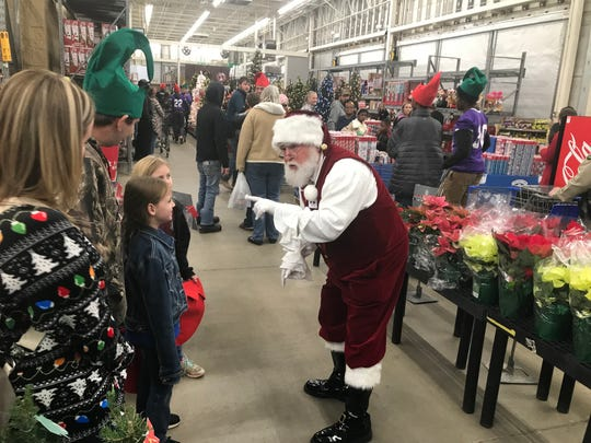 """Santa Claus sings """"Rudolph the Red-Nosed Reindeer"""" with a couple of shoppers at the Milan Wal-Mart on Tuesday night."""