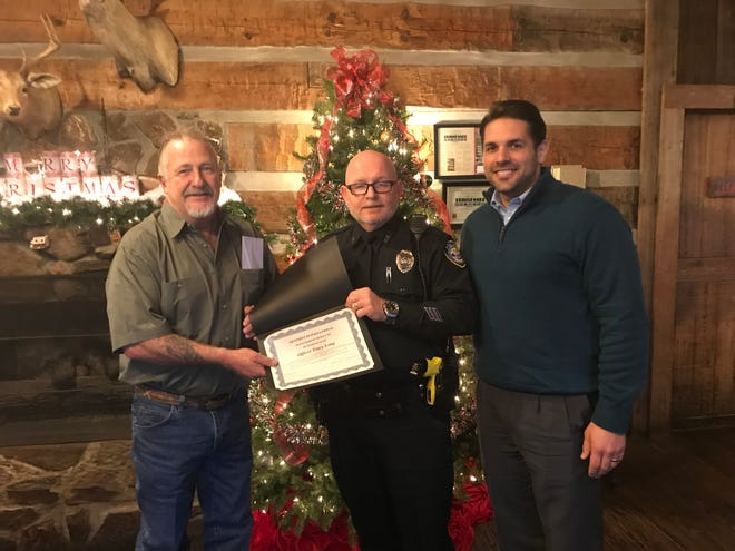 Jackson Police Officer Tracy Long accepts a certificate of appreciation from the Southside Optimist Club of Jackson along with Jackson Mayor Scott Conger.