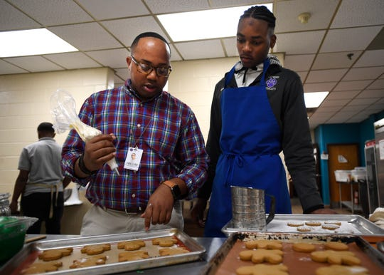 Tim Hayes shows Shocorius Sweet how to pipe icing on gingerbread cookies in his classroom at Haywood High School in Brownsville, Tenn on Tuesday, Dec. 10, 2019. Hayes teaches his students culinary arts and was also a contestant on the Netflix Series Sugar Rush.
