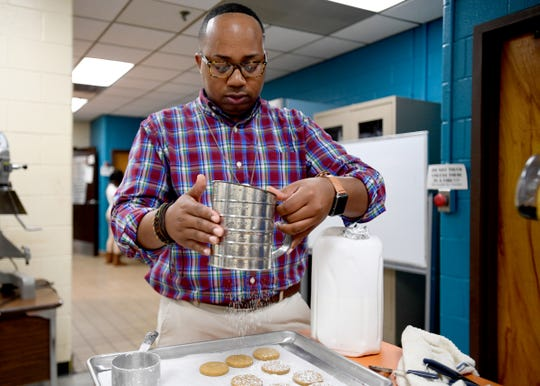Haywood High School Culinary Instructor Tim Hayes dusts some gingersnap cookies with powdered sugar during a class on Tuesday, Dec. 10, 2019. Hayes was also a contestant on the Netflix series Sugar Rush.