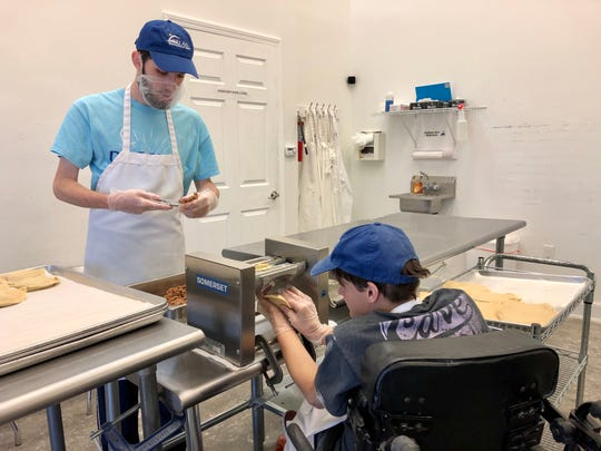 D.R.E.A.M.S. employees Lex Goulas and Logan Watkins make meat pies Wednesday, Dec. 11, at a small factory on Johnston Street.