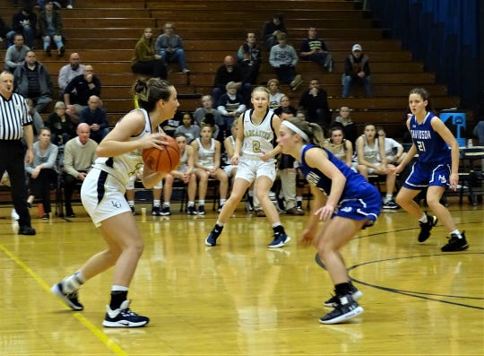 Lancaster senior guard Halle Spangler looks to pass the ball against a Hilliard Davidson defender as Ally Thompson  looks on during the Lady Gales' 49-47 win Tuesday night.