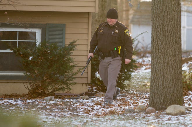 Livingston County Sheriffs Deputy Anthony Clayton carries a BB gun believed to be used in the shooting of a postal carrier on Crandall Road in Howell Township Wednesday, Dec. 11, 2019.