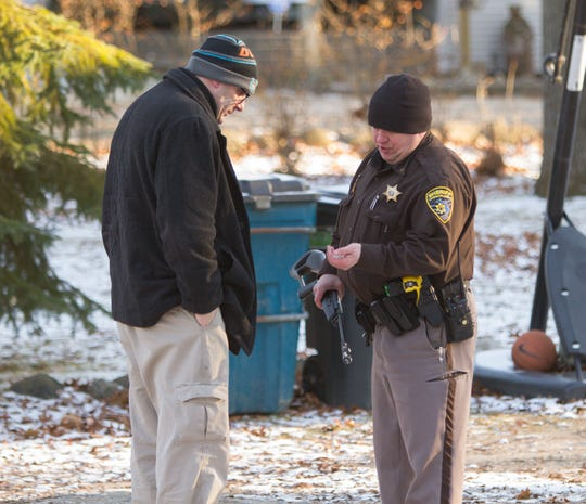 Livingston County Sheriffs Deputy Anthony Clayton shows a U.S. Postal Service employee a handful of cotton swabs thought to be initially used by a minor before using an BB gun to shoot a postal carrier in Howell Township Wednesday, Dec. 11, 2019.