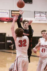 Brighton's Jacob Edwards shoots over Pinckney's Sean Packard on Tuesday, Dec. 10, 1019.